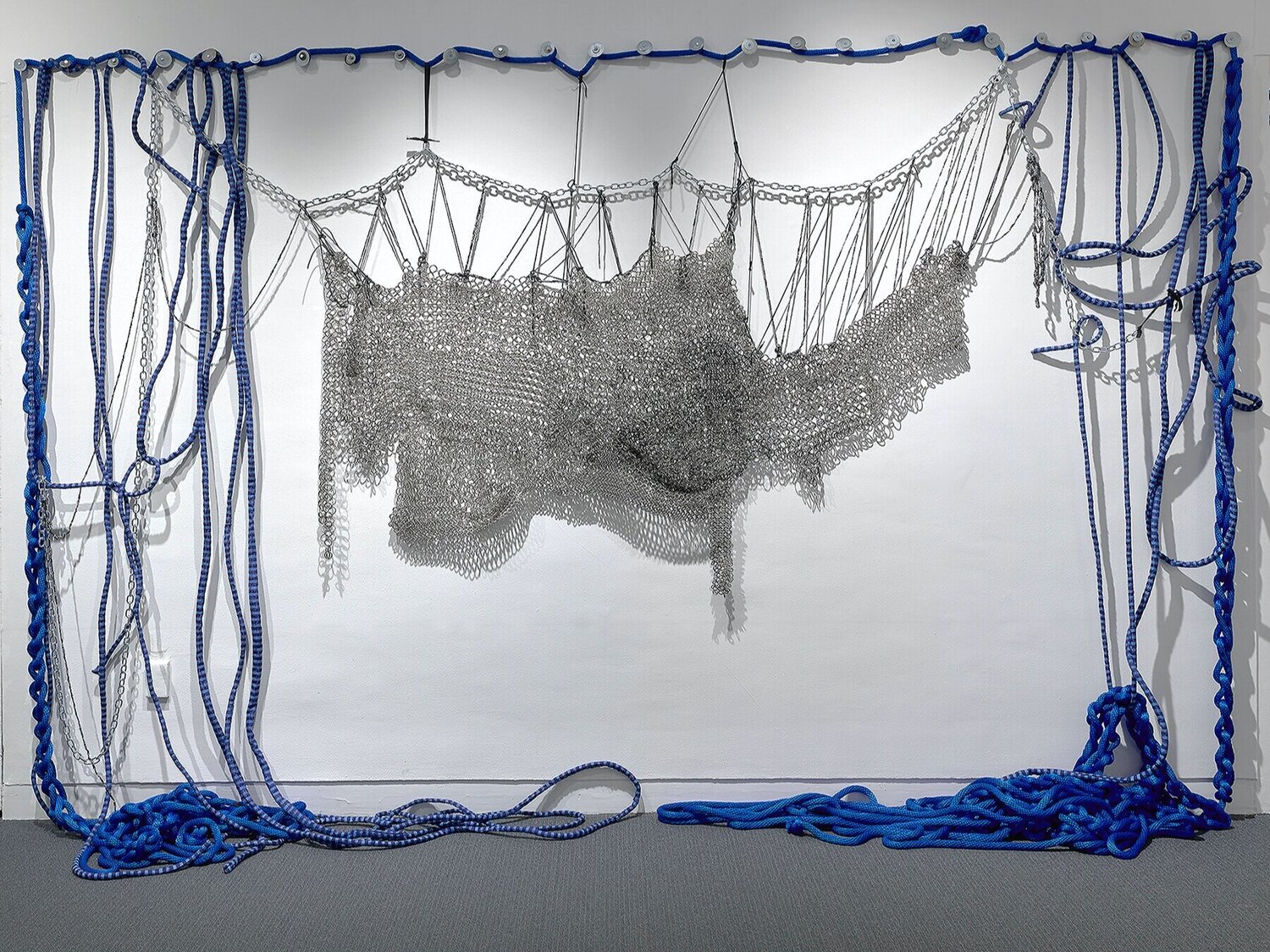 Blue rope on walls and floor with silver chains