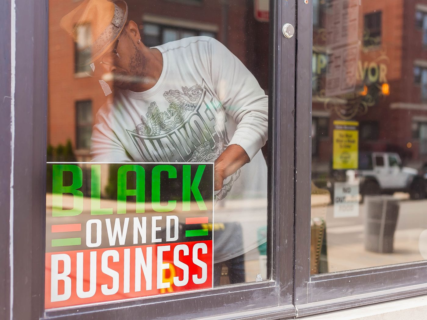 Man putting Black Owned Business sign in shop window