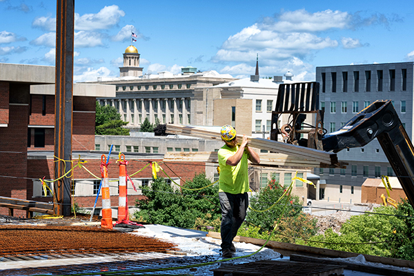 Image of a construction work carrying a wooden plank on the upper floor of a the construction site for the new Stanley Museum of Art. The Old Capitol dome can be seen in the background.