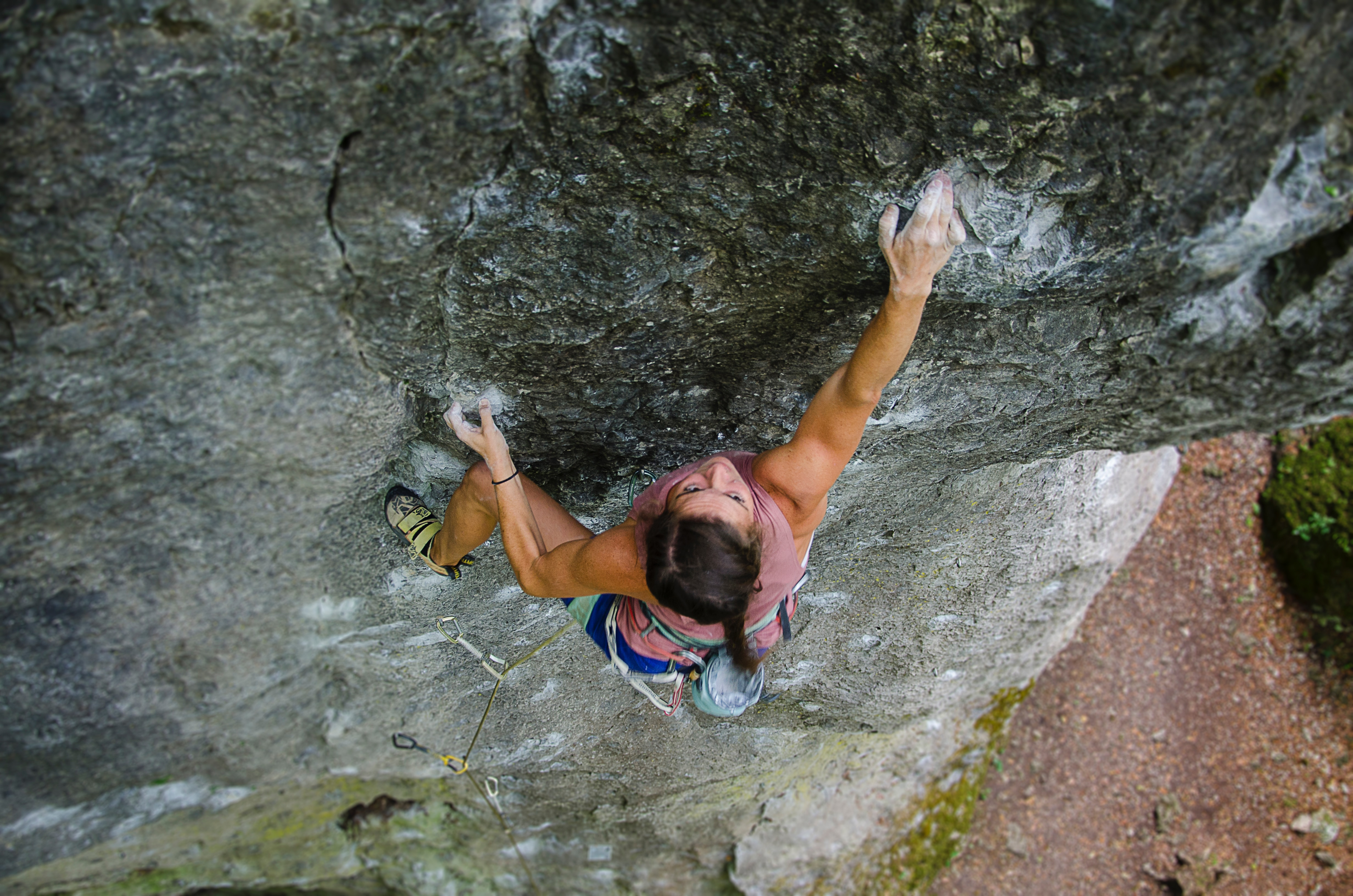 female mountain climber climbing up a cliff