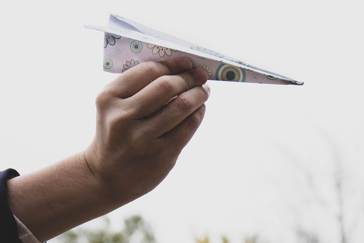 Collaborative Performance image. Hand holding a paper airplane.