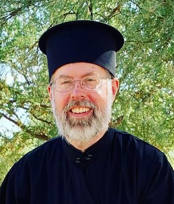 Portrait of Father Ignatius. He is wearing a black robe and hat and is smiling.