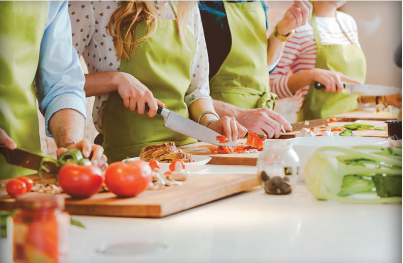 people cutting vegetables and wearing aprons