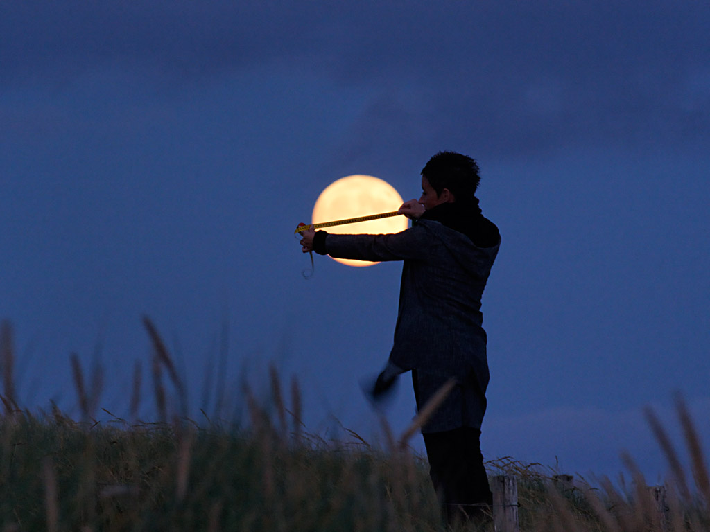 Person trying to measure moon with measuring tape